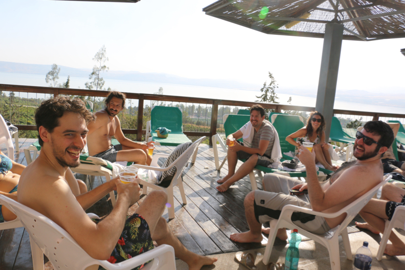 OnceHub employees sit by the pool enjoying a drink and company