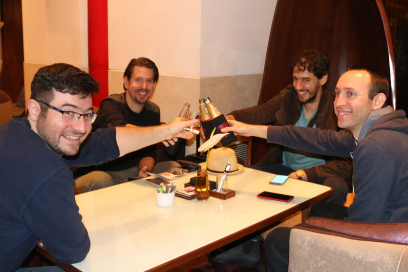 OnceHub employees sit together and enjoy a beer at the hotel bar