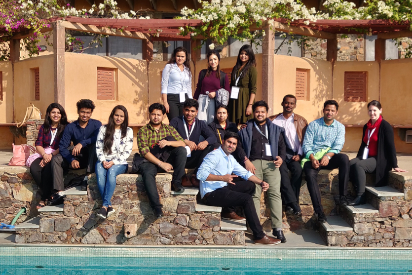 OnceHub employees pose in formal clothing in front of pool hotel
